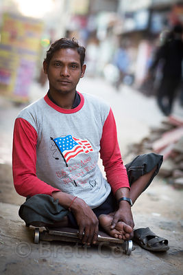 "Young man unable to walk due to polio wearing a ""USA"" shirt, Delhi, India"