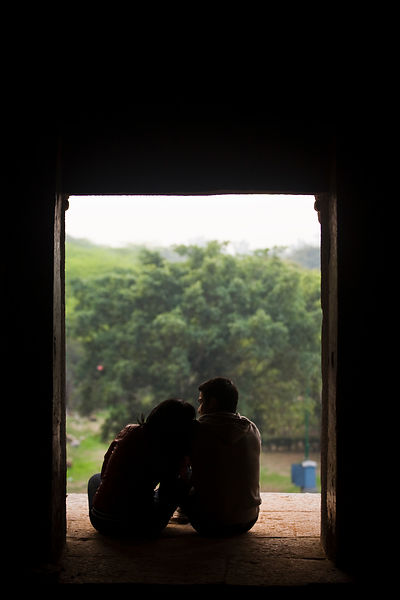 India - New Delhi - A young romantic couple sit in a window of the ruins of a Madrassa in Hauz Khas built by the 14th century Sultan Firoz Shah Tughlaq