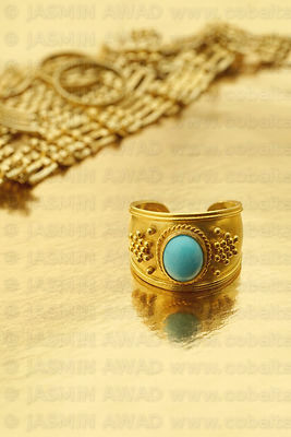 Gold ring with jewelry on gold background with copy space..