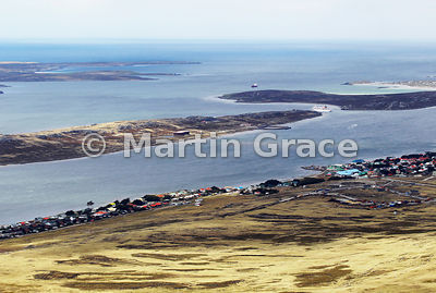 Stanley Harbour, East Falkland, from the air, with a cruise ship just leaving, Falkland Islands