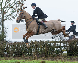 Adam Cooke jumping a hedge above Withcote