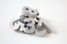 Pile of silver color metal numbers on white