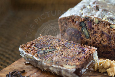 Sliced homemade date and walnut cake on wooden board and woven tray.