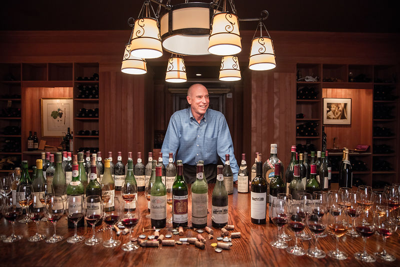 Michael Mondavi in his private cellar with several vintage wines photographed for Robb Report by editorial photographer Jason Tinacci