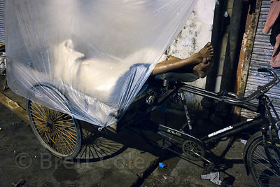 A cycle cart driver in sleeps in his cart in the Paharganj area of Delhi, India. A large percent of rickshaw and cart drivers in Delhi are homeless. This includes even auto rickshaw drivers.