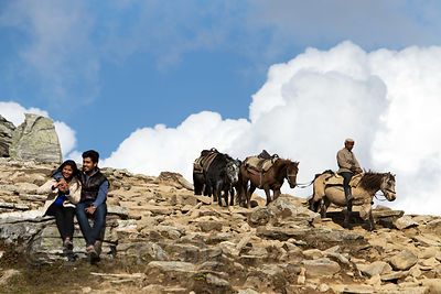 A coulple relax while a horseman leads horses down a slope at Rohtang Pass, Manali, India