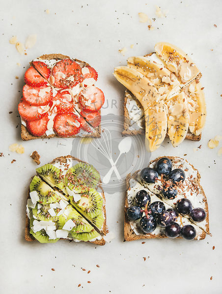 Wholegrain bread slices with cream cheese, various fruit, seeds and nuts