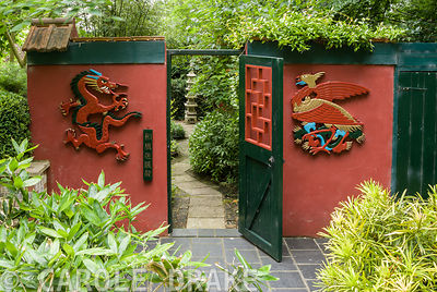 Three-Friends-of-Winter garden has a winter flowering plum, Prunus mume, at its centre and bamboo Sasa veitchii. Hand carved phoenix and dragon flank gate into Red Wall Garden. Beggars Knoll, Newtown, Westbury, Wiltshire, UK