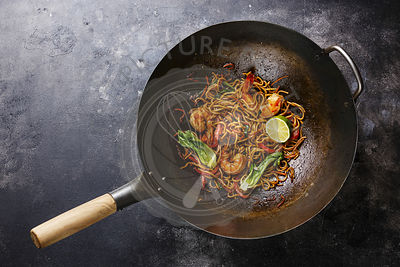 Udon noodles stir-fried with Tiger shrimps and vegetable in wok cooking pan on dark background