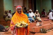 Smiling Muslim lady with bight headscarf holding a basket of Banana's. Rwanda