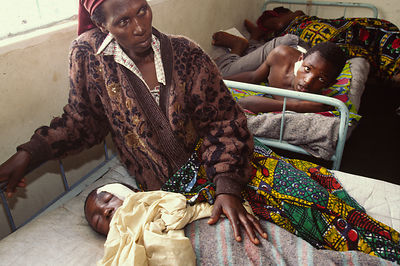 A mother in hospital caring for her two sons injured after an attack by the Interehamwe militia, Gisenyi, Rwanda