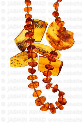 Amber beads necklace over polished amber pieces with tiny insect fossils Studio shot