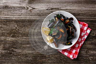 Mussels Clams and lemon on wooden background copy space