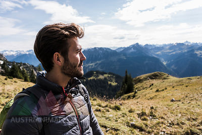 Austria, Tyrol, portrait of young man in mountainscape looking at view
