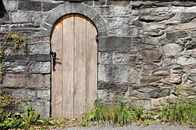 An old style wooden doorway amidst a stone wall in Bergen, Norway.