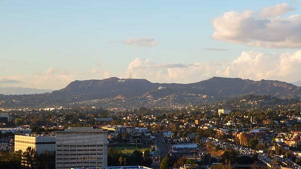Wide Shot: Sunset Over Hollywood, A Busy Highway, & Cloud Billowed Mountain Ranges (Pan)