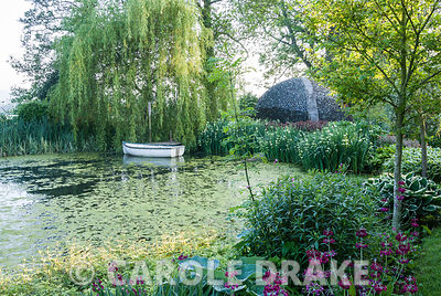 Lake edged with hostas and primulas contains small rowing boat below a weeping willow tree, with dome shelter made of glass bottles beyond. Westonbury Mill Water Garden, Pembridge, Herefordshire, UK