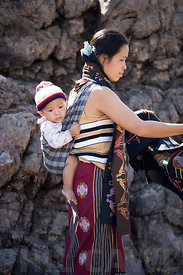 Laos - A young mother with her child strapped to her back.