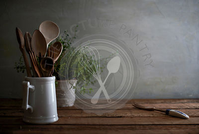 A still life image of a rustic, wood kitchen counter with wooden spoons in a porcelain vessel and a lovely, tangled oregano plant in the background.
