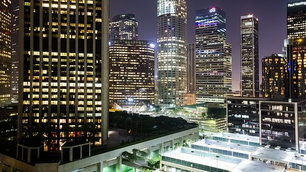 Medium Shot: An Evening In The Heart Of Downtown L.A. - Panning Traffic, Street Grids, High-Rises, & Searchlights