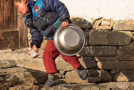 A boy washing up outside of the house in the morning in Phobjikha valley, Bhutan.
