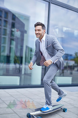 Portrait of smiling businessman skateboarding on pavement