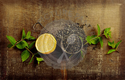 Dry tea with mint and lemon on wooden table, top view