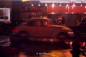 A speeding yellow car in New york on a wet rainy street at night