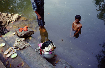 India - Kerala - A boy washes in the Backwaters