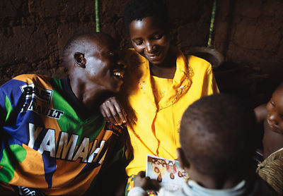 Rwanda - Kibileze - Jean Pierre Sibomana (31) who is HIV positive, talks with his wife and children who are HIV negative in Kanage village