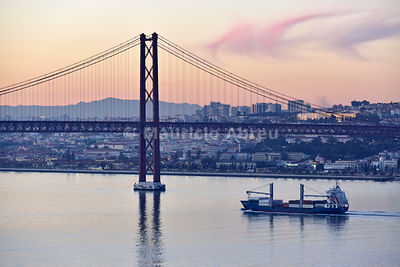 Lisbon and 25 de Abril bridge over the Tagus river, at dusk. Portugal