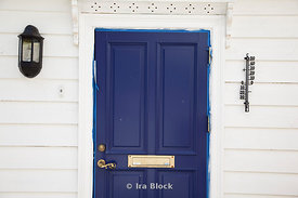 A recently painted blue door amongst a traditionally white home in Bergen, Norway.