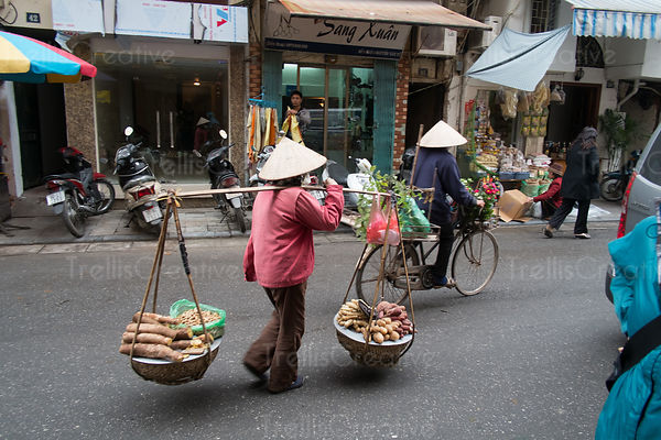 yam seller with wares in the basket walking down the street