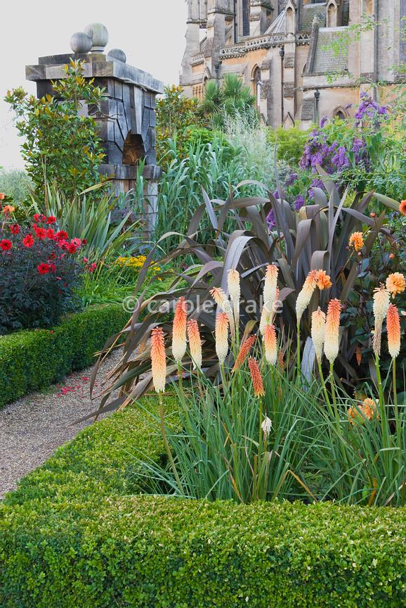 Lushly planted box edged borders include Kniphofia 'Painted Lady', dahlias, buddleia, phormiums and rudbeckia with Arundel Cathedral as backdrop. Arundel Castle Gardens, Arundel, West Sussex, UK