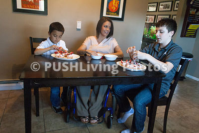 Young mother in a wheelchair making cupcakes with her children