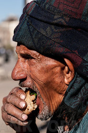 Old man eating a snack in Luxor.