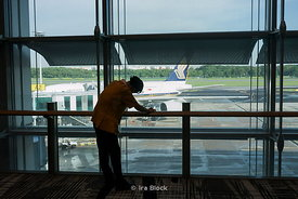 A cleaning lady wiping handrails at Changi Airport, Singapore.
