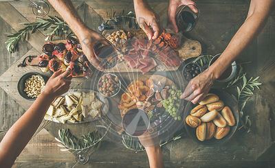 Top view of people having party, gathering, celebrating at wooden rustic table set with various wine snacks and fingerfoods