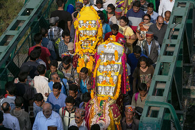 A crowd carry idols of Lord Raghunath over a bridge during the Dussehra festival in Kullu, India