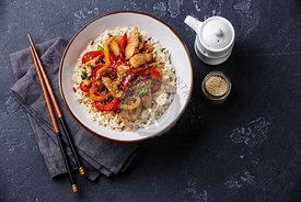 Stir-fry with chicken meat, vegetables and rice in bowl on dark stone background copy space