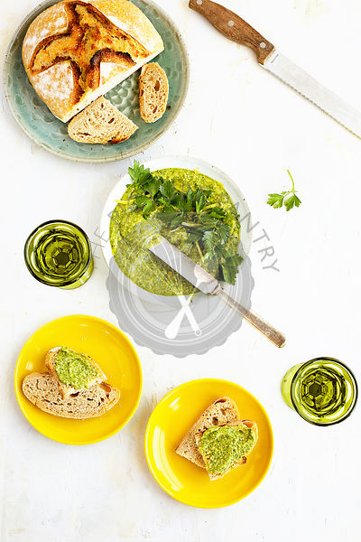Italian Parsley Lemon Pesto served in a ceramic bowl with sourdough bread and wine.