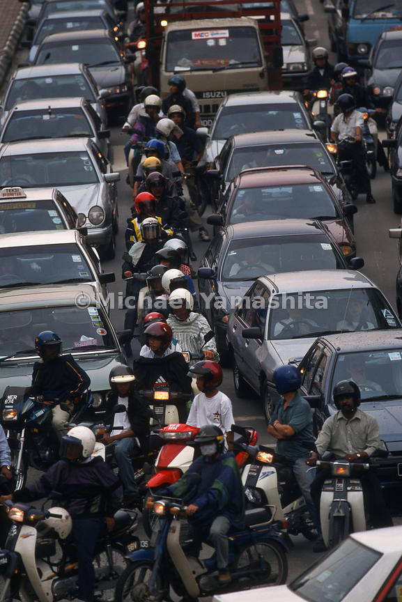 The congestion of cars and motorcycles between lanes makes it difficult to move anywhere.