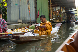 A monk at a floating market called Damnoen Saduak Floating Market in Damnoen Saduak District, Ratchaburi province, about 109 kilometers south of Bangkok.