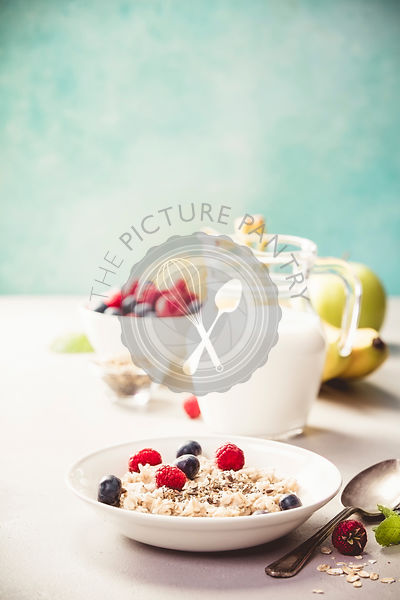 Oatmeal porridge with fresh berries, fruits and almond milk. Healthy breakfast, healthy eating, vegan food concept.