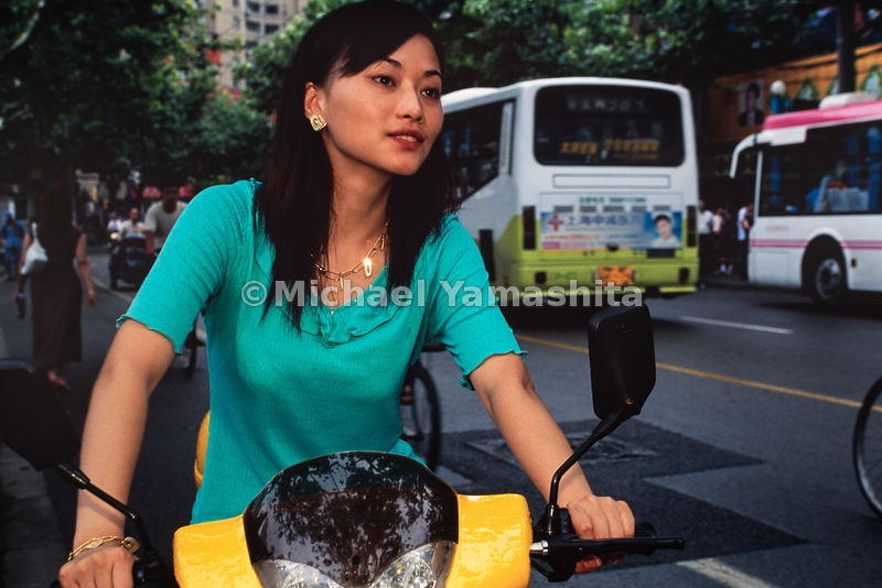 Young lady riding motorbike around residential district of Shanghai, China.