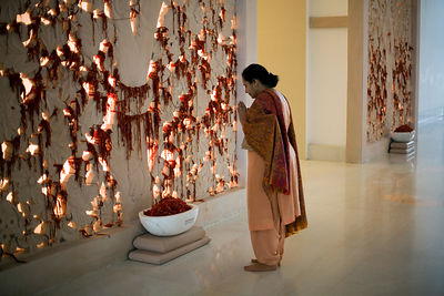 India - Gurgaon - A woman offers prayers at a prayer wall in the Medicity hospital