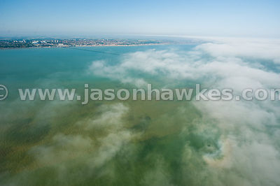 Aerial view over clouds looking down onto seascape