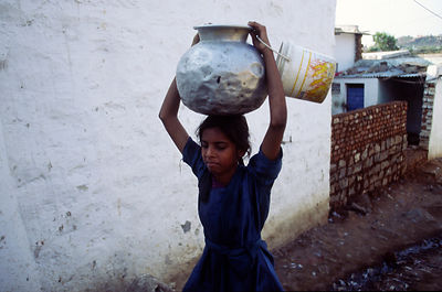 Child carries water in a slum, Hydrabad, India