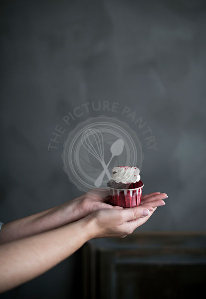 A red cupcake being held in a woman hands