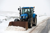 Farmer on a New Holland tractor clearing snow oiff rural road after a snowstorm. Cumbria, UK.